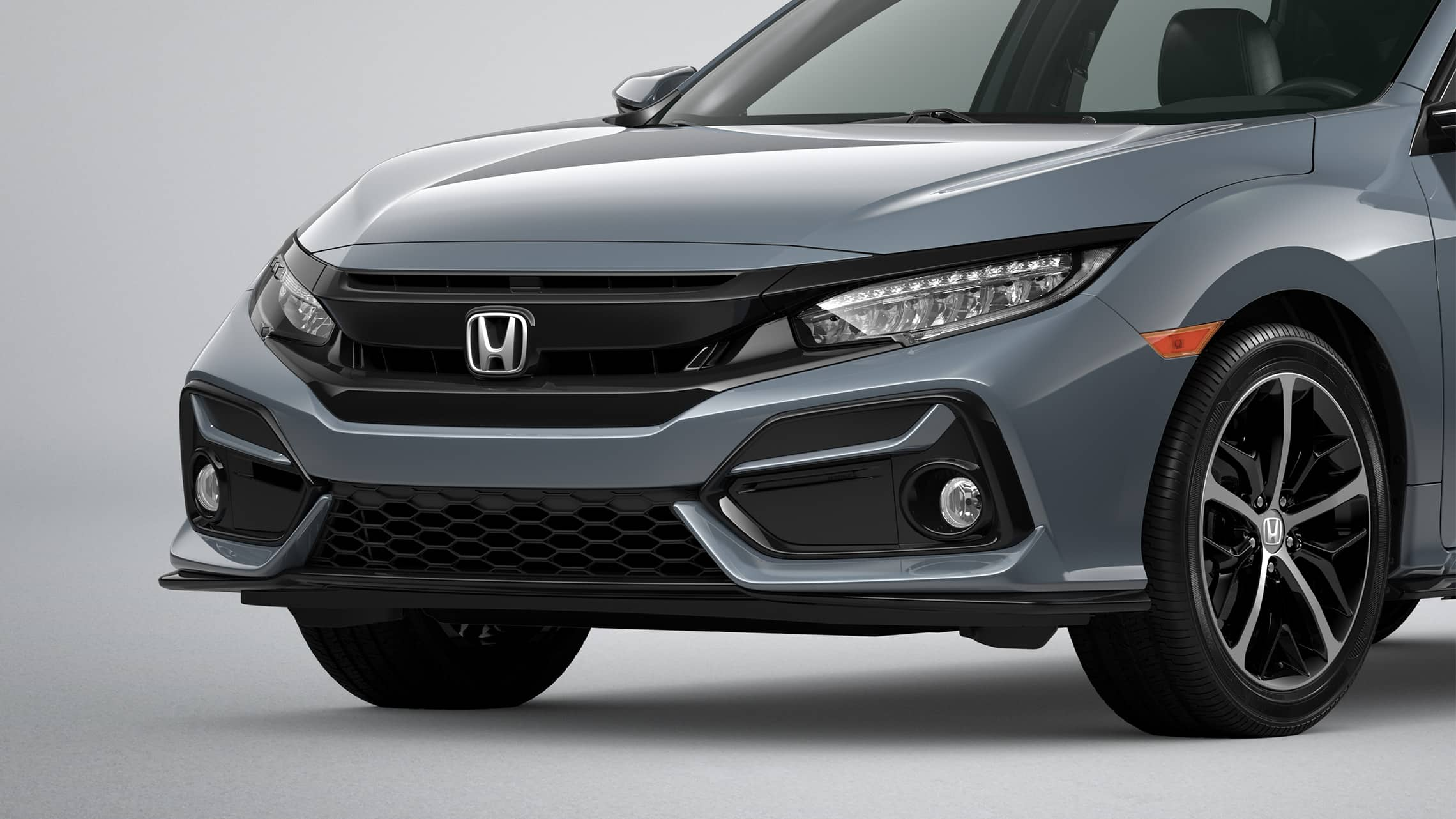 Primer plano frontal del lado del conductor del Honda CivicSportTouringHatchback2021 en Sonic Gray Pearl.