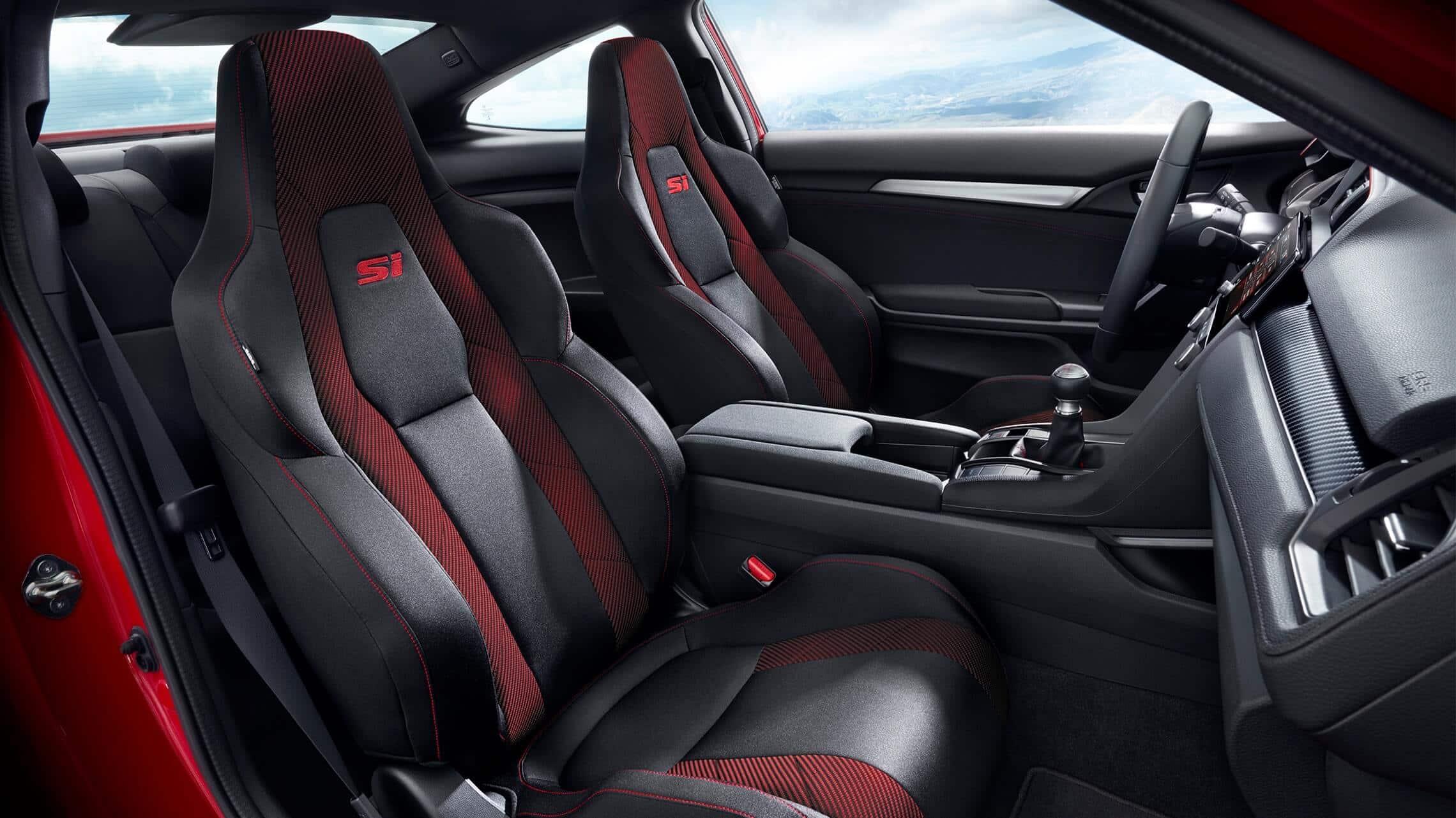 Vista interior desde el lado del pasajero de los asientos delanteros acojinados en el Honda Civic Si Coupé2020 en Black Cloth con detalles en rojo.