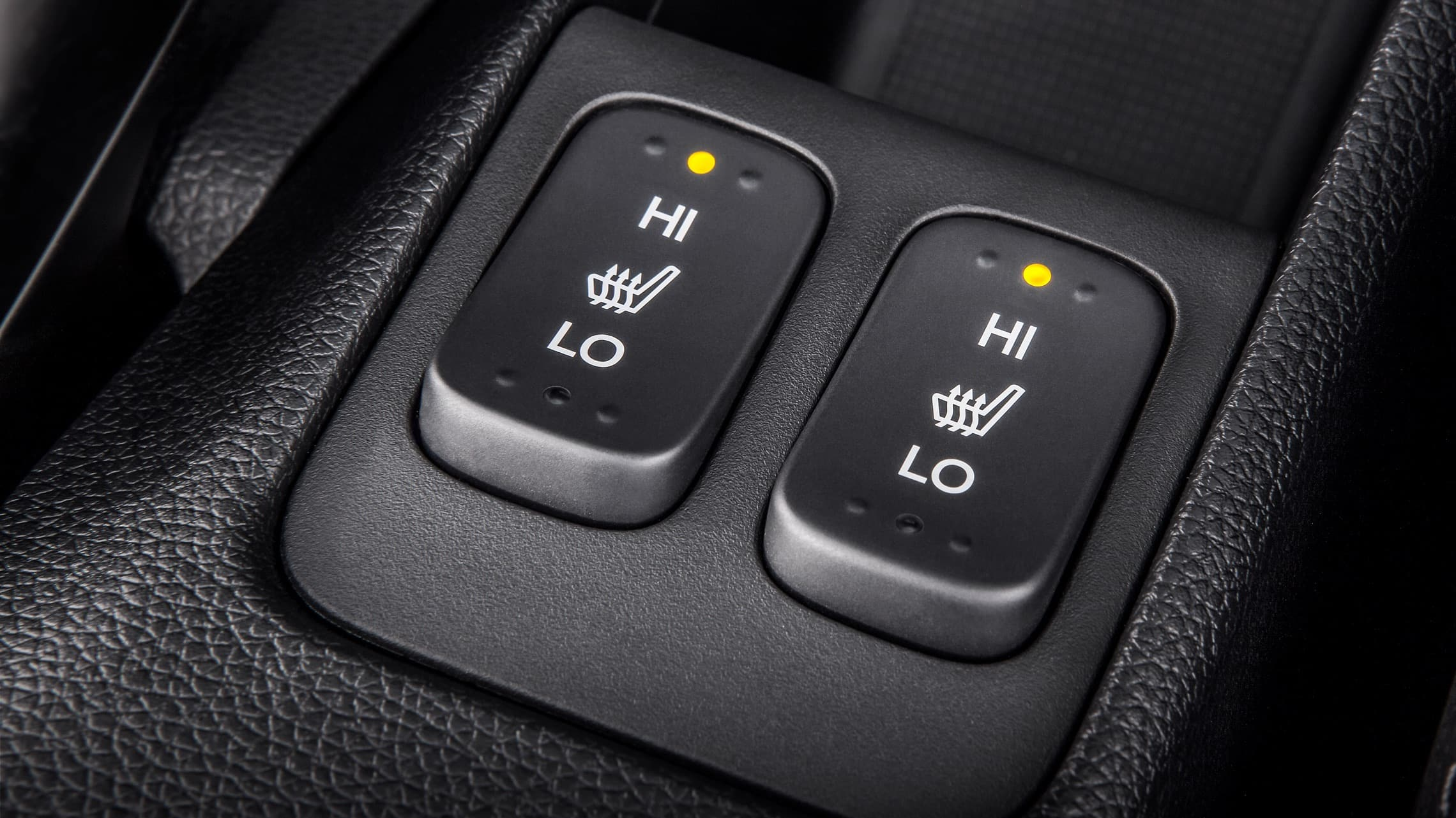 Detalle de los botones del control de los asientos delanteros con calefacción del Honda Fit EX-L 2020.