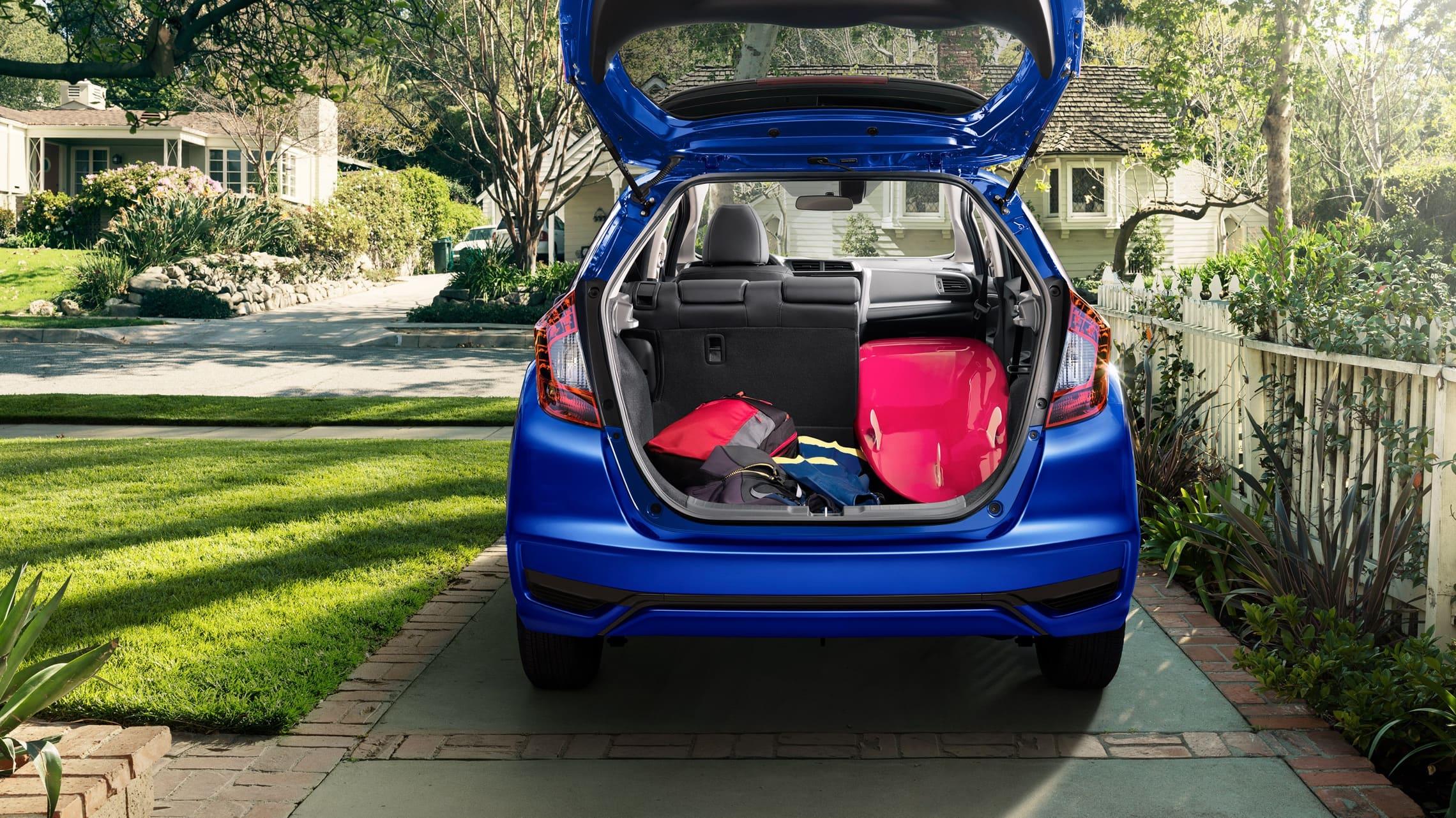 Vista trasera del Honda Fit EX-L2020 en Aegean Blue Metallic con la puerta trasera abierta y una tabla de surf en el área de carga.