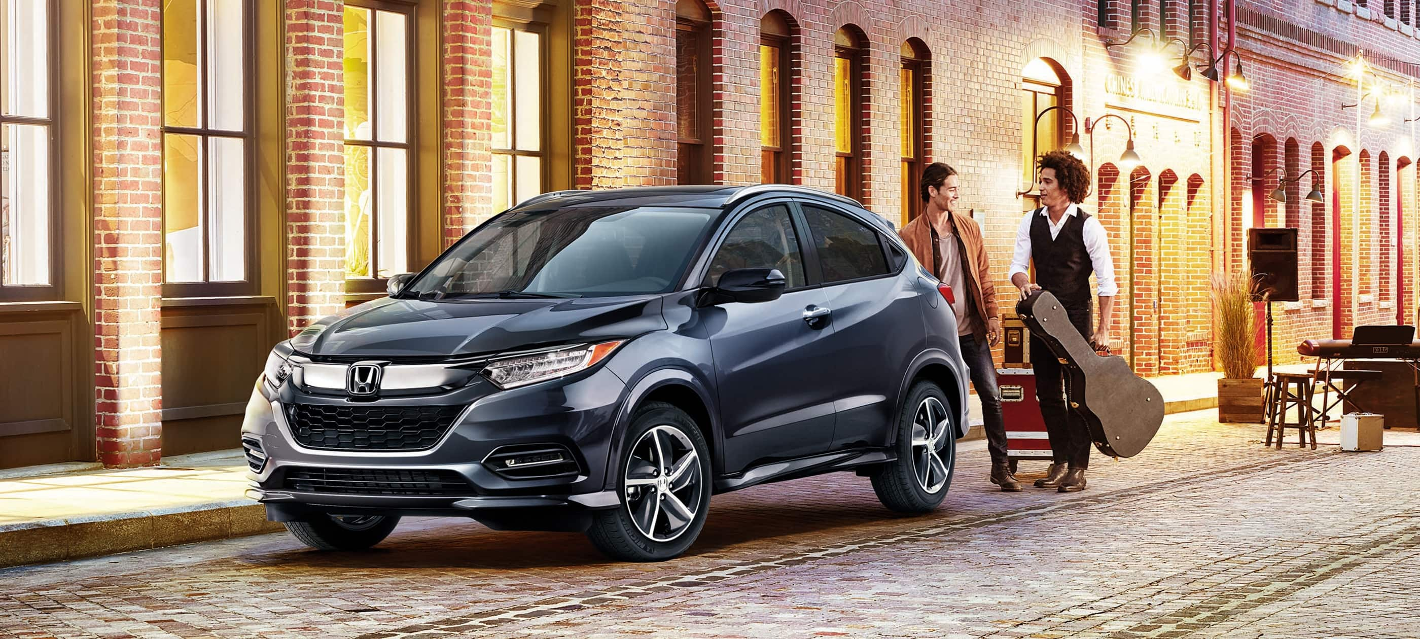 Front driver-side view of the 2020 Honda HR-V Touring in Modern Steel Metallic parked on a city road.